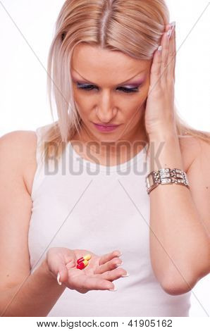 Beautiful blonde holding pills in one hand and with other holding the head because of headaches