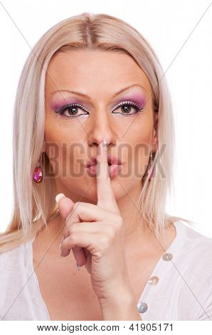 Beautiful blonde showing shush with index finger on the lips, isolated on white