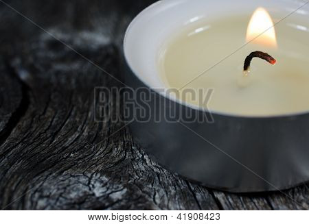 Close-up Photograph Of A Lit Tea Light Candle On An Old Wooden Board