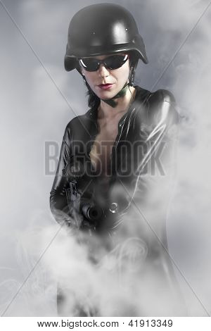 Sexy girl holding gun with helmet over smoke