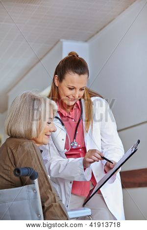 Doctor in clinic asking senior woman in wheelchair for a signature
