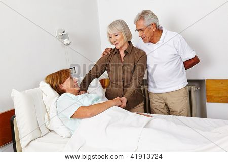Senior people visiting bedridden woman in sickbed in a hospital