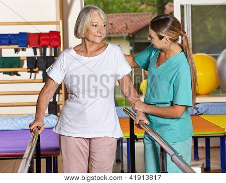 Senior woman at kinesiotherapy with physiotherapist in nursing home