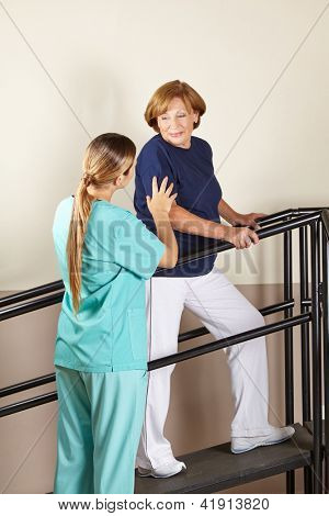 Physiotherapist doing kinesiotherapy with senior woman on railing