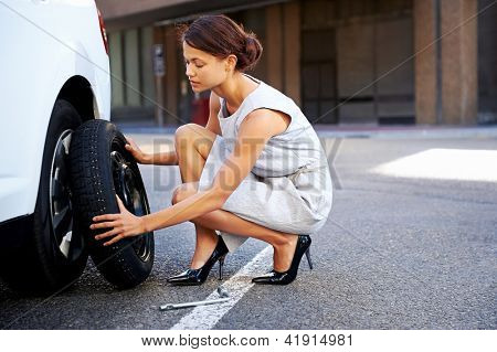 businesswoman in the city with flat tire frustrated