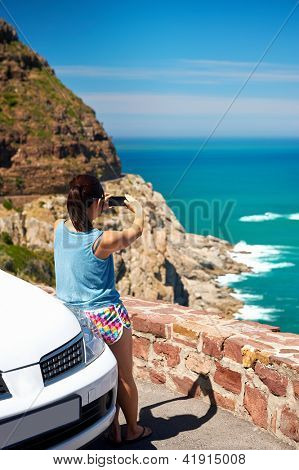 Tourist woman taking a photograph of scenic ocean mountain road chapmans peak in cape town south africa with rental car