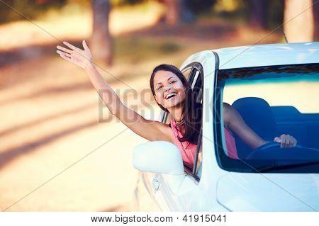 Mujer feliz saludando desde el asiento del conductor en el coche mientras viaja