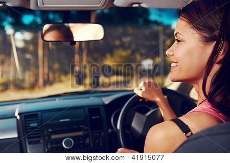 Woman driving on vacation on country road happy and smiling