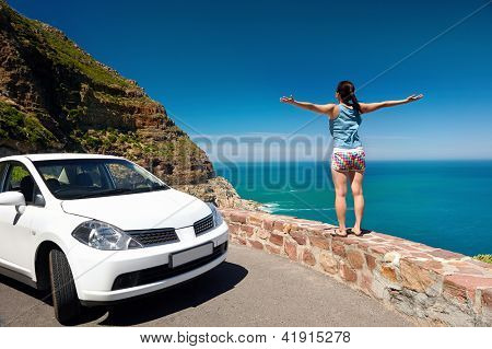 carefree tourist stands on chapmans peak drive with arms outstretched in freedom girl pose with rental car
