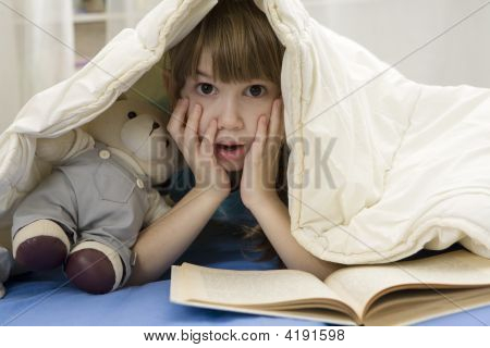 Little Girl With Bear Is Reading The Book On Sofa