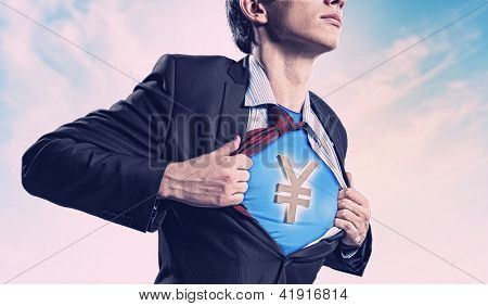 Image of young businessman in superhero suit with yen sign on chest