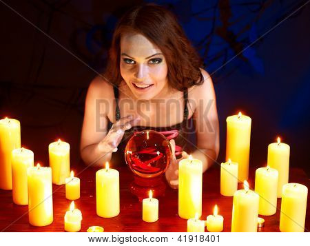 Woman holding scrying ball and candle.