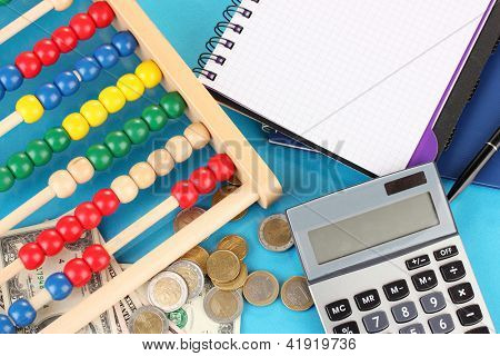 Bright wooden abacus and calculator. Conceptual photo of old and modern business