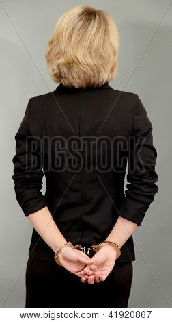 Young beautiful business woman in handcuffs on grey background