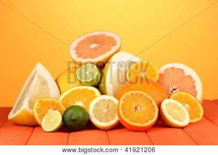 Lots ripe citrus on wooden table on orange background