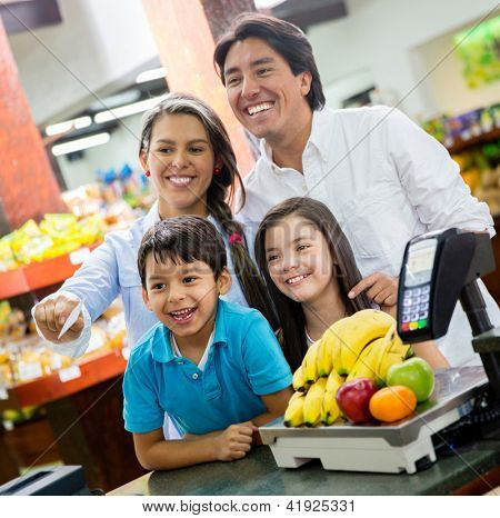 Happy family paying for groceries at the supermarket
