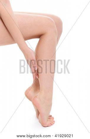 jovem mulher tocando suas belas pernas com mão sobre fundo branco