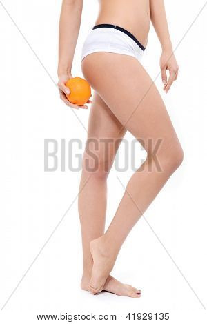 Young woman in underwear with an orange showing absence of cellulite over white background