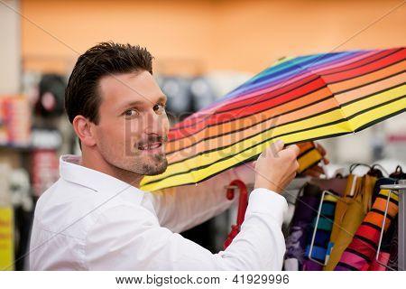 Retrato de hombre guapo sonriendo mientras compra paraguas en supermercado