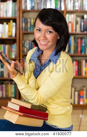 Student - a young woman or girl with pile of books learning in library and reading e-book on tablet computer