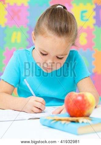 Cute little girl is writing using a pen