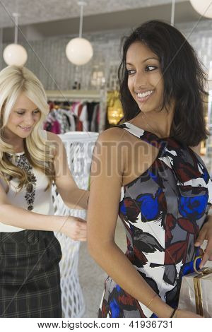 Store assistant helps an Indian female customer with her dress in shop