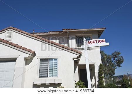 House with 'Auction Sign' against blue sky