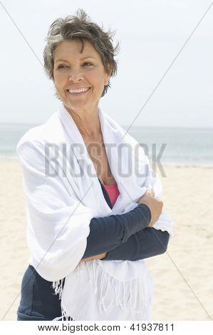 Happy senior woman wrapped with stole at beach