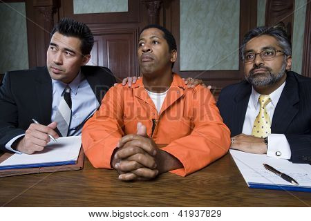 Advocates and client listening to case in courtroom