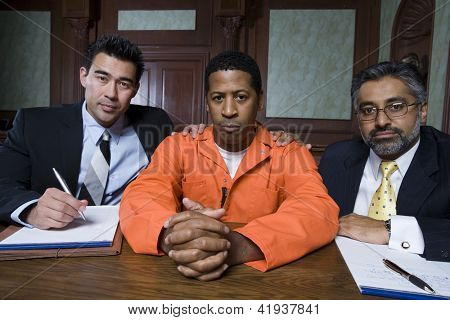 Portrait of criminal and his advocates sitting together in courtroom