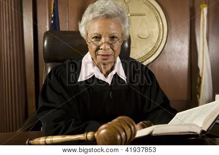 Senior judge sitting with book in courtroom