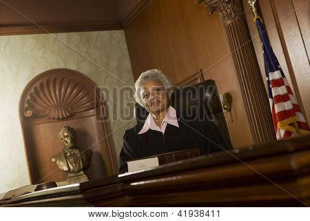 Portrait of happy senior judge sitting in courtroom
