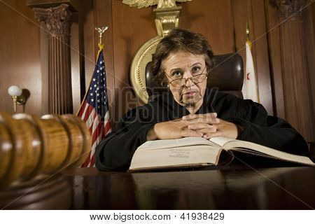 Portrait of senior judge with book in courtroom