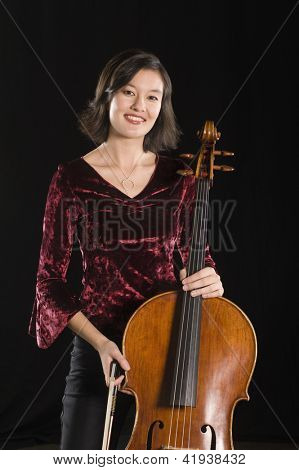 Portrait of a beautiful woman standing with cello classical musical instrument