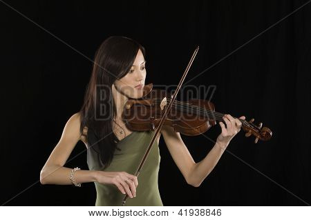 Beautiful young female playing violin isolated over black background