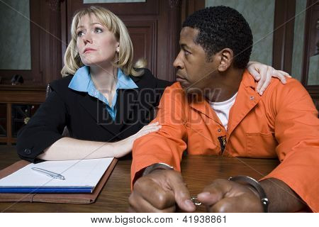 Female advocate with prisoner listening case in courtroom