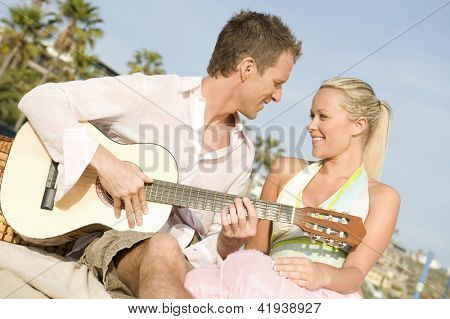 Young man serenading his girlfriend while playing guitar