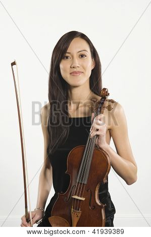 Portrait of happy beautiful female standing with violin and fiddlesticks isolated over white background