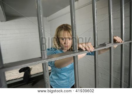 Upset businesswoman standing behind bars in jail