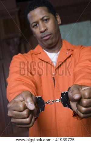 Close de mãos do prisioneiro restringida com algemas