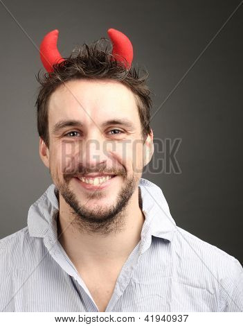 Young man in the image of cunning devil in studio.