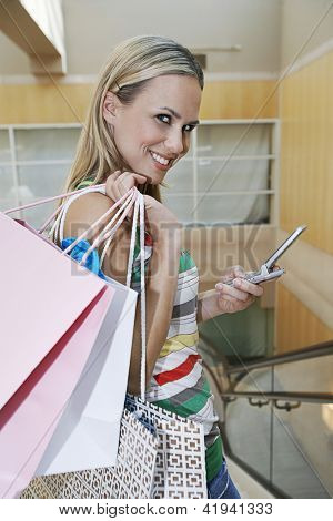 Portrait of blonde woman posing with shopping bags and cell phone