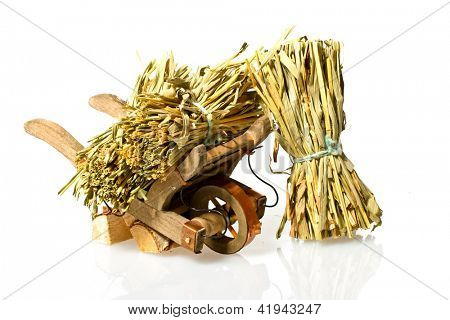 Handcart with straw on a white background