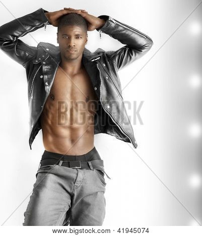Fashion portrait of a good looking young fit male model in trendy clothes against modern background with copyspace