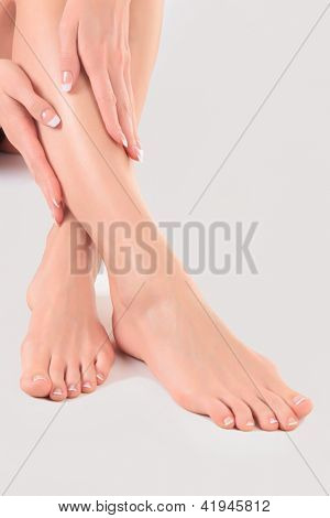 Well-groomed hands on female feet. Main focus is on the hands