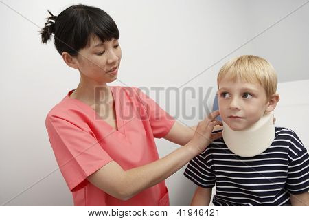 Female doctor tying neck brace to boy in clinic