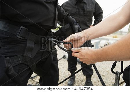 Man's hand fixing harness on commando's waist