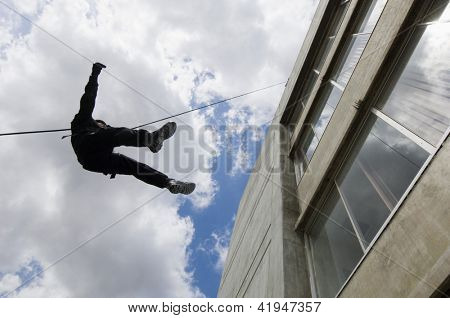 Military man rappelling down the rope from building