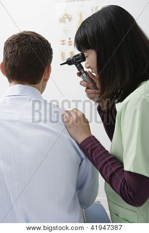Female doctor checking patient ear with otoscope