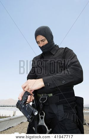 Commando preparing his handgun on military training